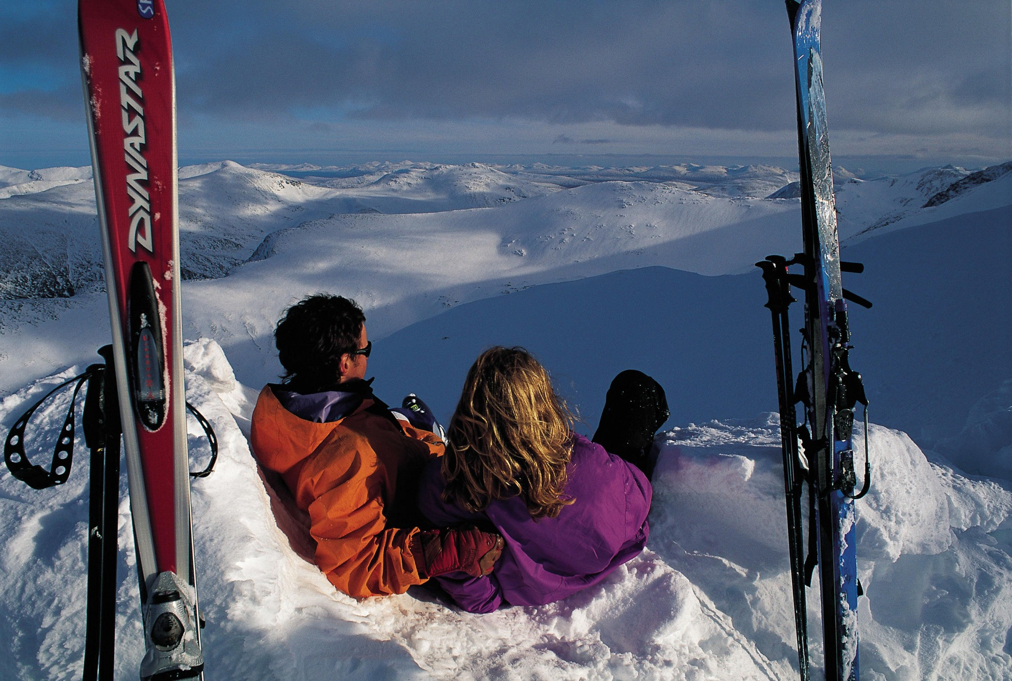 Free use stock 2 skiers snuggle up in snow hole at Nevis Range Credit VisitScotland, ScottishViewpoint